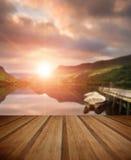 Sonnenaufgang über See mit Booten machte an der Anlegestelle mit hölzernen Planken fest Stockfoto