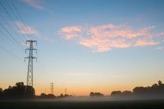 Sonnenaufgang über Stromleitungen Lizenzfreie Stockfotos