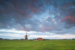 Sonnenaufgang über Windmühle auf niederländischem Ackerland Stockbild
