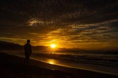Sonnenaufgang auf dem Strand mit einem schönen hintergrundbeleuchteten Himmel stockbilder