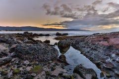 Sonnenaufgang auf den Felsen nahe dem Ozean Stockfotos