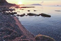 Sonnenaufgang auf der kieseligen Küste Lizenzfreie Stockbilder