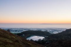 Sonnenaufgang auf einem eisigen, nebelhaften Wintermorgen Betrachten eines Reservoirs über der englischen Landschaft Malvern Hüge stockfotos