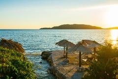 Sonnenaufgang auf einem schönen Strand mit Sonnenschutz Stockfotografie