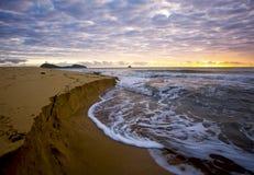 Sonnenaufgang auf einem Steinhaufen-Strand Stockfotos