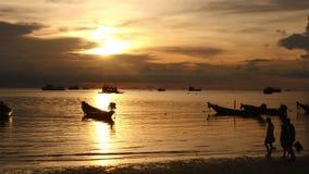Sonnenaufgang auf einem tropischen Strand Schattenbilder von Booten und Leute, Sand und Meer stock video