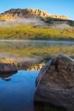 Sonnenaufgang auf See mit Bären zum Butte im Hintergrund, Montana Stockfotos
