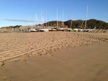 Sonnenaufgang auf Strand mit Segelbooten Stockfotos