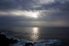 Sonnenaufgang über dem Ozean durch die Wolken mit den Wellen, die Al zerschmettern Lizenzfreie Stockfotos