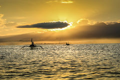 Sonnenaufgang über dem Ozean nahe Lovina-Strand, Bali Fischerboote I Stockfotografie