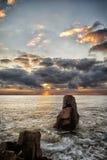 Sonnenaufgang über einem felsigen Strand Bunte Wolken, die im Meer sich reflektieren Drastischer Sonnenaufgang über dem Schwarzen Stockbilder