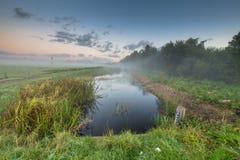 Sonnenaufgang über Fluss mit messender Stange des Wasserspiegeles Stockbild