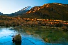 Sonnenaufgang des frühen Morgens, Landschaftslandschaft von gefrorenem blauem reinem Wassersee, wilde Berge und enormer Vulkan mi stockfotos