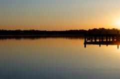Sonnenaufgang am Dock auf dem Fluss Stockfoto