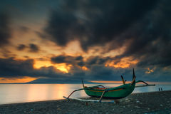 Sonnenaufgang an einem Strand mit Fischerboot im Vordergrund Lizenzfreies Stockbild