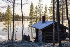 Sonnenaufgang gesehen im Wald hinter Holzhaus, Finnland Lizenzfreie Stockfotos
