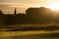 Sonnenaufgang-Golfplatz-Übungsgrün, Autumn Dew auf Flagge Stockbilder