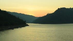 Sonnenaufgang hinter Berg auf Fluss in Thailand stock footage