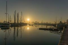Sonnenaufgang im Hafen von Valencia, die Sonnenaufgänge zwischen angekoppelten Segelbooten und Frachthafenkränen Stockfotos