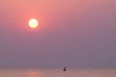 Sonnenaufgang im Meer mit einem Schattenbildfischerboot Lizenzfreies Stockbild