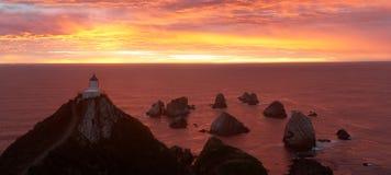Sonnenaufgang im Nugget-Punkt mit Leuchtturm stockbilder