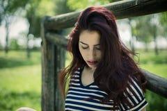 Sonnenaufgang, junges Mädchen mit dem Strohhut, der herein auf einer Holzbrücke sitzt Stockbild