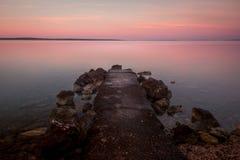 Sonnenaufgang-Kroatien-Strand mit Pastellfarbe Rocky Jetty stockfotos