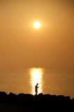 Sonnenaufgang mit einem Fischer und einem kleinen Lastkahn auf Horizont, Caorle, Italien Stockfotos