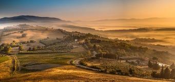 Sonnenaufgang mit Nebel über toskanischem Dorf Stockfotos