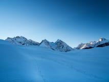 Sonnenaufgang mit schneeweg in einer Hochgebirgsregion der Schweizer Alpen Stockbild
