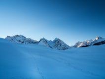 Sonnenaufgang mit Schneeweg in einer hoher Gebirgsregion im Schweizer Al Lizenzfreie Stockbilder