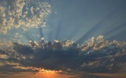 Sonnenaufgang mit Sonne hinter Wolken mit einem blauen Himmel im Hintergrund Lizenzfreie Stockfotografie