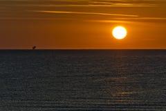 Sonnenaufgang mit Sonne und Bohrinsel Stockbild