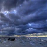 Sonnenaufgang, schlammiger Strand und Boote lizenzfreies stockfoto