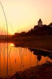 Sonnenaufgang-Sonnenuntergang über ruhigem Wasser Stockfotos