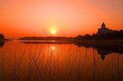 Sonnenaufgang-Sonnenuntergang über ruhigem Wasser Stockbild