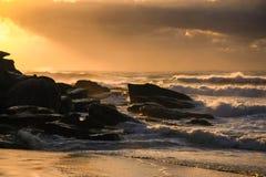 Sonnenaufgang und Brandung am Strand Stockfotografie