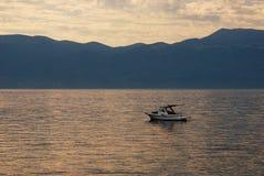 Sonnenaufgang und ein einsames Boot auf dem Meer Lizenzfreies Stockbild