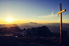 Sonnenaufgang und Gipfel kreuzen an Hochkönig-Berg, Österreich Stockfotografie