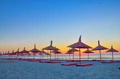 Sonnenaufgang unter Sonnenschirm auf dem Strand Stockbild