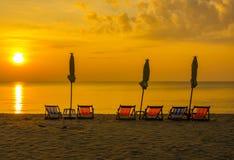 Sonnenaufgang unter Sonnenschirm auf dem Strand Stockfoto