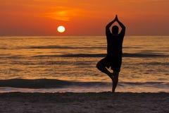 Sonnenaufgang-Yoga-Baum-Haltungs-Mann-Schattenbild-Meditation Stockfotos