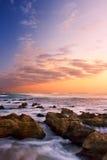 Sonnenaufganglandschaft von Ozean mit Wellenwolken und -felsen Stockfotos