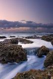 Sonnenaufganglandschaft von Ozean mit Wellenwolken und -felsen Lizenzfreies Stockbild