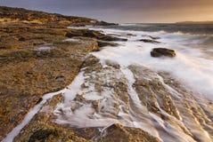 Sonnenaufganglandschaft von Ozean mit Wellenwolken und -felsen Stockbilder
