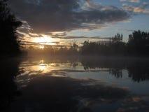 Sonnenaufgangreflexion auf Morgennebelsee Stockbild
