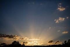 Sonnenaufgangsonnenstrahlen durch die Wolken vom Horizont, Kopienraum, Tapete Stockbilder