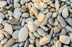 Sonnenbeschiene kleine Steine auf dem Seeufer Lizenzfreie Stockfotografie