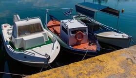 Sonnenbeschiene rote, weiße, grüne und blaue Mittelmeerfischerboote auf Wasser in Euboea - Nea Artaki, Griechenland lizenzfreie stockfotografie