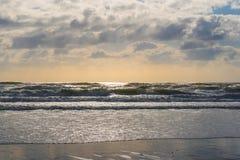 Sonnenbeschiene Wellen am Strand Lizenzfreie Stockbilder